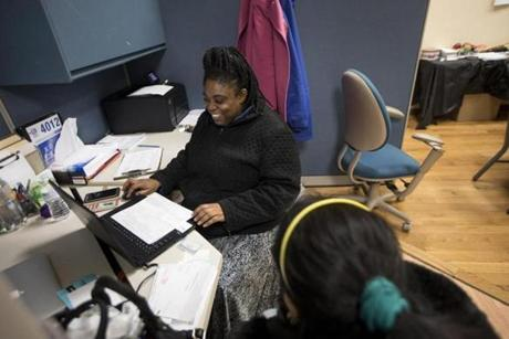 Mercy Nunez looked over tax documents for a client at Community Economic Development Center in New Bedford.